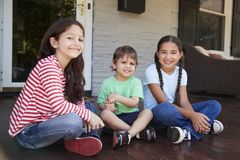 Portrait des enfants s'asseyant sur le porche de la Chambre ensemble photographie stock libre de droits