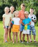 Portrait des enfants se tenant avec des jouets sur le pré vert en parc image stock