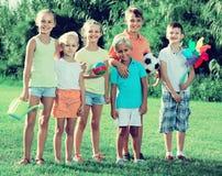 Portrait des enfants se tenant avec des jouets sur le pré vert en parc Images stock
