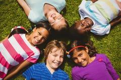 Portrait des enfants se trouvant sur l'herbe au parc Photos libres de droits