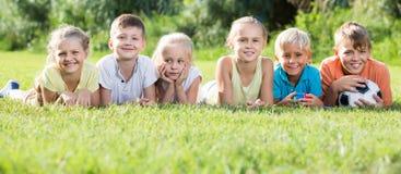 Portrait des enfants se trouvant sur l'herbe en parc et semblant heureux Images libres de droits