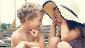 Portrait des enfants sur la plage en été Petite fille dans un chapeau parlant à son frère et sourire Ils se reposent Image libre de droits