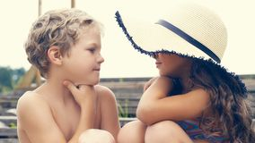 Portrait des enfants sur la plage en été Petite fille dans un chapeau parlant à son frère et sourire Ils se reposent Photos stock