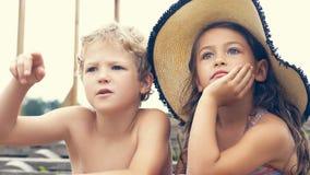 Portrait des enfants sur la plage en été Petite fille dans un chapeau parlant à son frère et sourire Ils se reposent Photo libre de droits