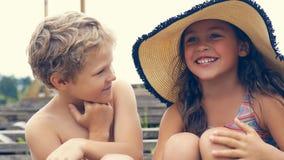 Portrait des enfants sur la plage en été Petite fille dans un chapeau parlant à son frère et sourire Ils se reposent Photographie stock