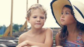 Portrait des enfants sur la plage en été Petite fille dans un chapeau parlant à son frère et sourire Ils se reposent Photo stock