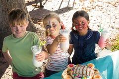 Portrait des enfants tenant des boissons tout en se tenant à la table en parc Images stock