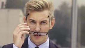 Portrait des entsetzten Gesch?ftsmannes Junger hübscher kaukasischer Mann in den Überraschungstriebgläsern und Blicke auf die Kam stock video