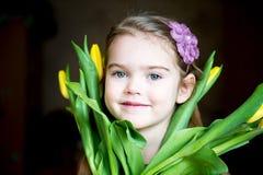 Portrait des entzückenden sonnigen Kindmädchens mit Tulpen Lizenzfreies Stockfoto