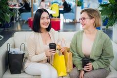 Portrait des femmes de sourire avec les paniers et le café pour aller regarder l'appareil-photo le centre commercial photos libres de droits