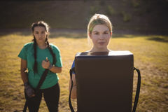 Portrait des femmes tenant l'équipement de boxe pendant le parcours du combattant Image stock