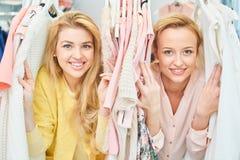 Portrait des filles de sourire dans le magasin avec des vêtements Image stock