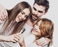 Portrait des filles heureuses et des types chantant dans le microphone au-dessus du fond blanc Photo stock