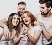 Portrait des filles heureuses et des types chantant dans le microphone au-dessus du fond blanc Images stock