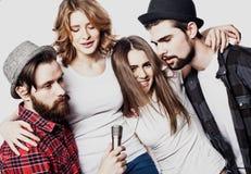 Portrait des filles heureuses et des types chantant dans le microphone au-dessus du fond blanc Photo libre de droits