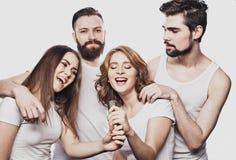 Portrait des filles heureuses et des types chantant dans le microphone au-dessus du fond blanc Photos stock