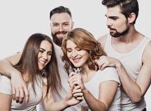 Portrait des filles heureuses et des types chantant dans le microphone au-dessus du fond blanc Photos libres de droits