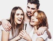 Portrait des filles heureuses et des types chantant dans le microphone au-dessus du fond blanc Images libres de droits