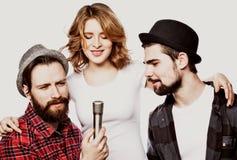 Portrait des filles heureuses et des types chantant dans le microphone au-dessus du fond blanc Photographie stock