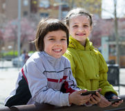 Portrait des filles heureuses jouant avec des téléphones Photographie stock