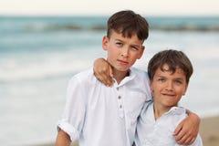 Portrait des frères heureux dans des chemises blanches sur le fond de la mer Photo stock