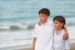 Portrait des frères heureux dans des chemises blanches sur le fond de la mer Photographie stock libre de droits