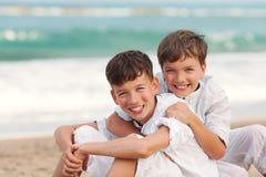 Portrait des frères heureux dans des chemises blanches sur le fond de la mer Image stock