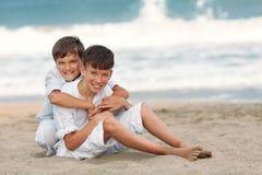 Portrait des frères heureux dans des chemises blanches sur le fond de la mer Images libres de droits