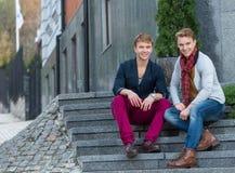 Portrait des frères jumeaux à la mode élégants s'asseyant sur le sta Images libres de droits