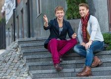 Portrait des frères jumeaux à la mode élégants s'asseyant sur le sta Photographie stock libre de droits