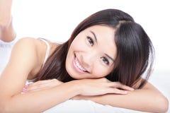 Portrait des Frauenlächelngesichtes, das auf Bett liegt Stockbilder