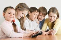Portrait des garçons et des filles drôles à l'aide des dispositifs numériques ensemble à la table à la maison images libres de droits