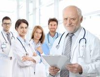 Portrait des gealterten Doktors mit medizinischen Bewohnern Lizenzfreie Stockbilder