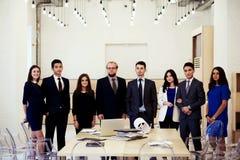 Portrait des gens d'affaires ethniques multi posant tout en se tenant dans la table proche intérieure de bureau moderne avec le d Photos stock