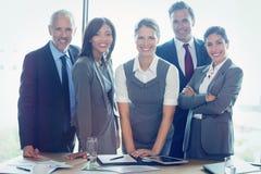 Portrait des gens d'affaires se tenant ensemble dans la salle de conférence Images stock