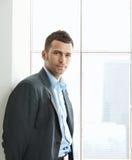 Portrait des Geschäftsmannes am Bürofenster Stockfotos