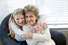 Portrait des glücklichen jungen Mädchens, das Großmutter umarmt Stockfoto