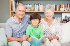 Portrait des grands-parents avec le petit-fils tout en tenant le livre Images stock