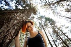 Portrait des hübschen Redheadmädchens in den Bäumen Lizenzfreie Stockfotografie