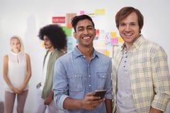 Portrait des hommes d'affaires de sourire utilisant le téléphone portable avec des collègues photographie stock libre de droits