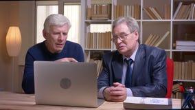 Portrait des hommes d'affaires sup?rieurs s'asseyant ensemble ? la table fonctionnant avec l'ordinateur portable et discutant s?r clips vidéos