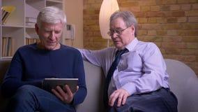 Portrait des hommes d'affaires sup?rieurs s'asseyant ensemble sur le sofa observant dans le comprim? et discutant joyeux banque de vidéos