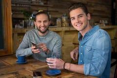 Portrait des hommes de sourire s'asseyant à la table dans le café Photos stock