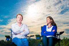 Portrait des hommes et des femmes de se reposer dans une chaise extérieure Image stock