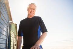 Portrait des huttes se tenantes prêt de sourire de plage d'homme supérieur Photographie stock libre de droits