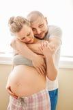 Portrait des jeunes couples caucasiens blancs riants de sourire de Moyen Âge, femme enceinte avec le mari dans la chambre étreign Image stock