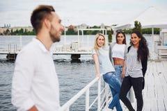 Portrait des jeunes et heureux au repos sur le pilier Amis appréciant un jeu sur le lac Émotions positives Photo stock