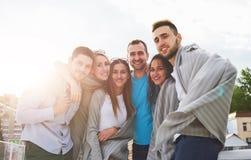 Portrait des jeunes et heureux au repos sur le pilier Amis appréciant un jeu sur le lac Émotions positives Photos stock