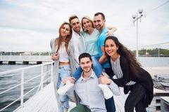 Portrait des jeunes et heureux au repos sur le pilier Amis appréciant un jeu sur le lac Émotions positives Photos libres de droits