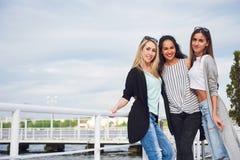 Portrait des jeunes et heureux au repos sur le pilier Amis appréciant un jeu sur le lac Émotions positives Images stock